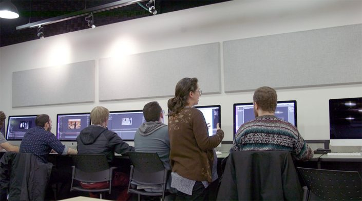 A woman with long brunette hair and glasses wearing a brown sweater stands next to students in a computer lab