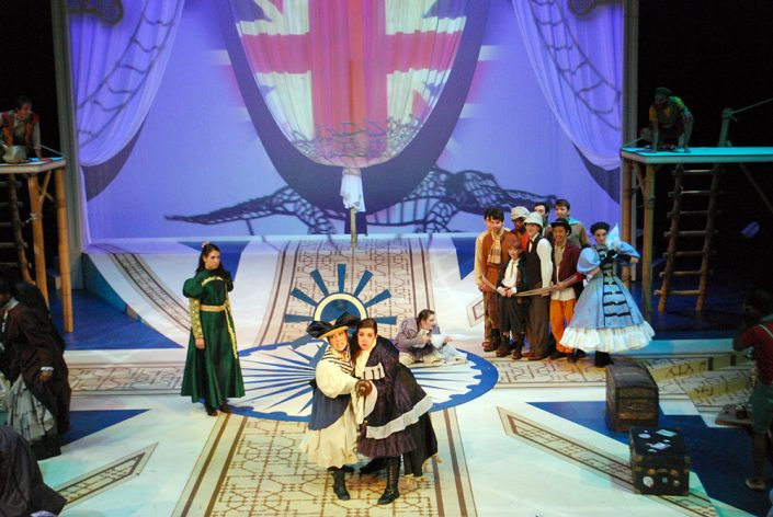 Actors in colonial dresses stand on the stage, a large sail has a projection of the British flag on it.