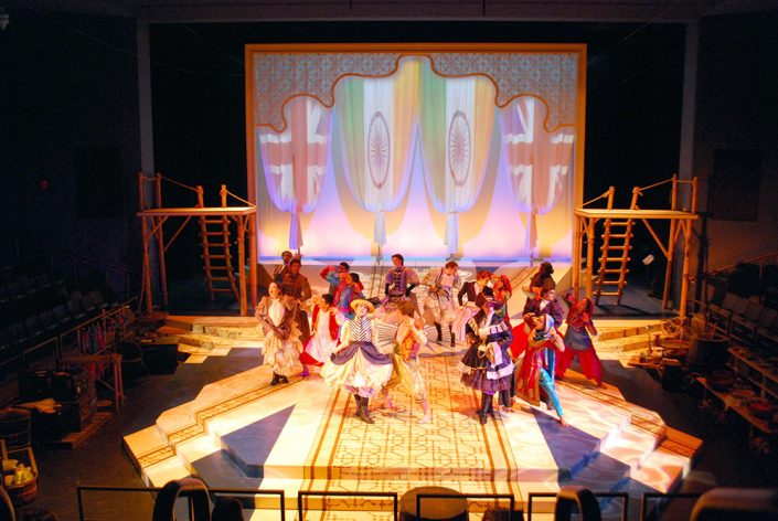 A crows of actors wearing colonial clothing and middle eastern clothing stand in the middle of a stage.