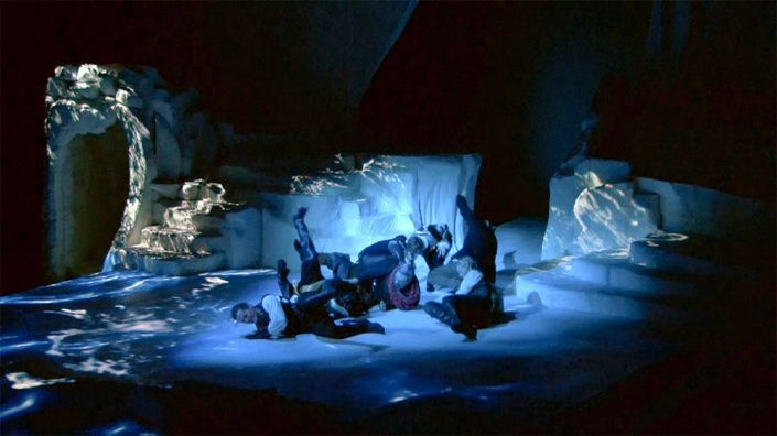 A group of people fall down on stage with projections of water around them