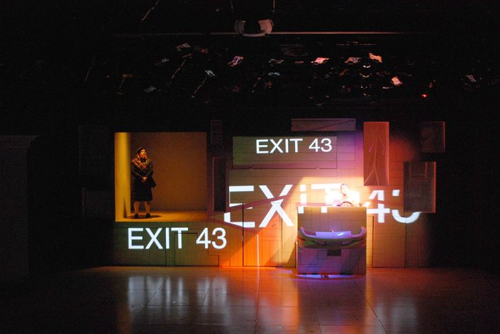 """A man steers a pretend car on stage as large words that say """"exit 43"""" are projected around him."""