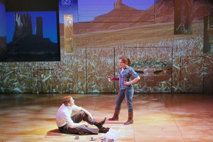 A woman in a plaid shirt and jeans holding a beer can talks to a man seated on the stage. The projected background is of a corn field.