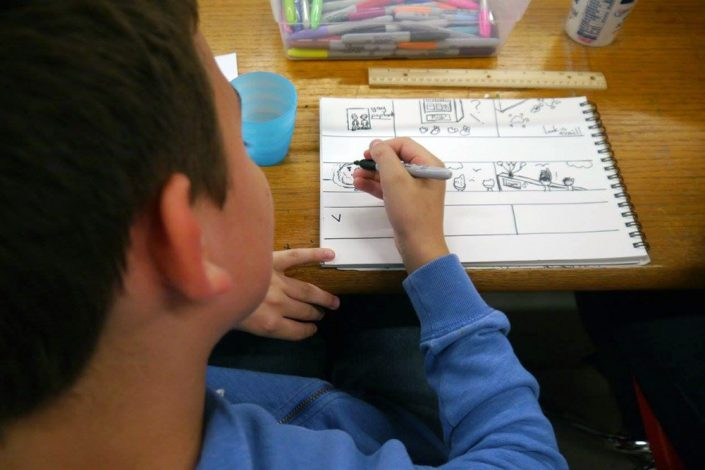 A boy in a blue shirt drawing with a black marker on a pad of paper.