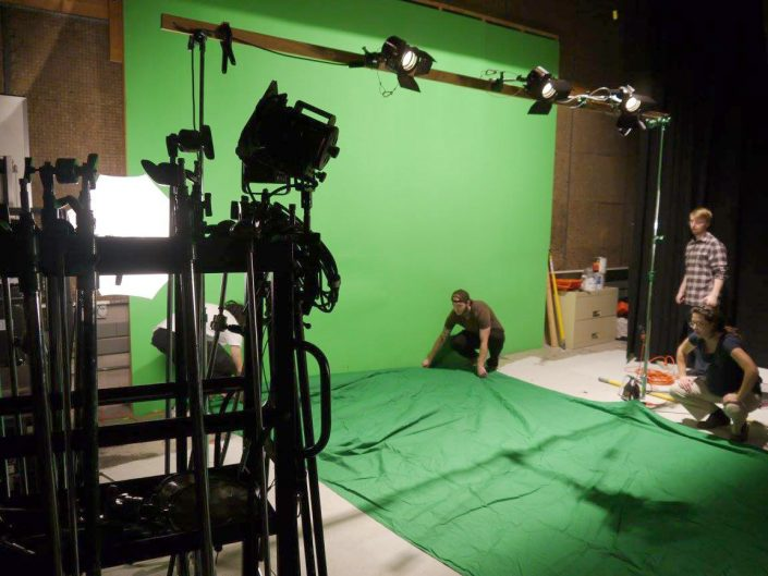 Four people setting up a green screen in a lit studio