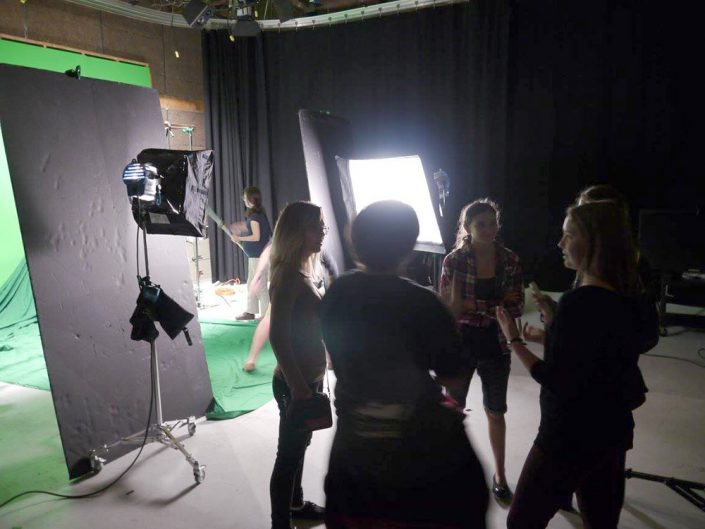 Five people standing in a circle talking next to bright studio lights and a green screen.