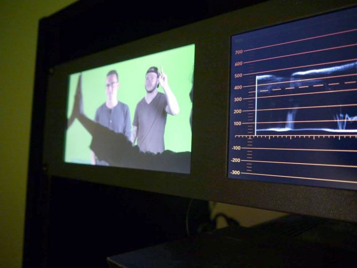 A camera monitor showing a diagram and two men standing in front of a green screen.