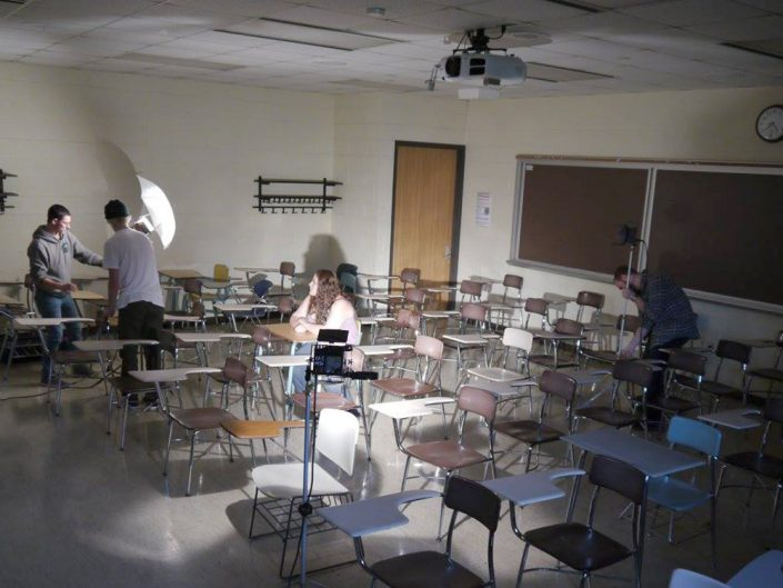 A classroom full of empty desks and one girl sitting in the middle of them. Three people around her are setting up studio lights in the classroom.